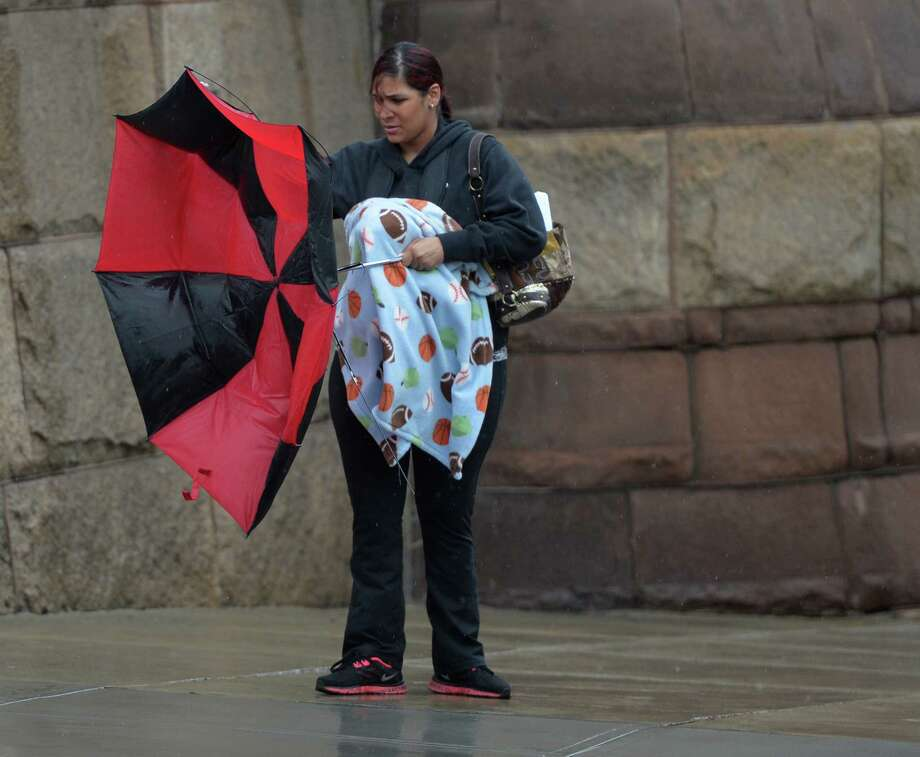 Maria Santisteban fights with her failing umbrella during the rains and wind that overtook the city Tuesday afternoon April 15, 2014 in Albany, N.Y.  (Skip Dickstein / Times Union) Photo: Skip Dickstein
