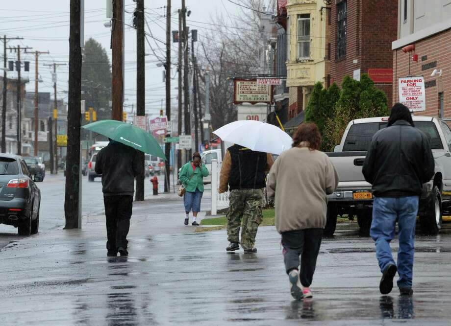 Pedestrians walk down State St. in the rain on Tuesday, April 15, 2014 in Schenectady, N.Y.  (Lori Van Buren / Times Union) Photo: Lori Van Buren