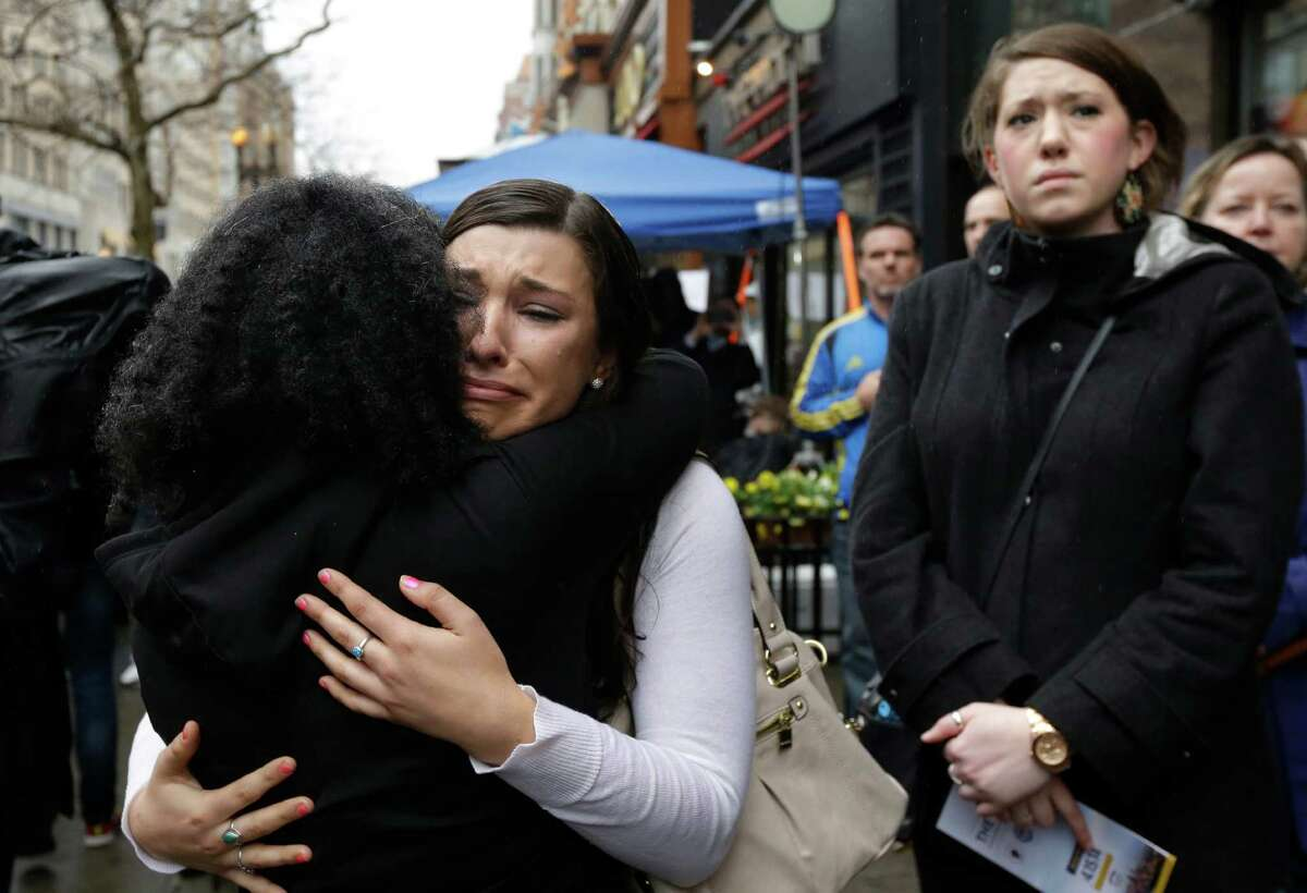 Olivia Savarino, center, hugs Christelle Pierre-Louis, left, as Callie Benjamin, right, looks on near the finish line of the Boston Marathon during ceremonies on Boylston Street, Tuesday, April 15, 2014, in Boston. Savarino and Benjamin were working at the Forum restaurant when a bomb went off in front of the building on April 15, 2013. (AP Photo/Steven Senne) ORG XMIT: MASR106