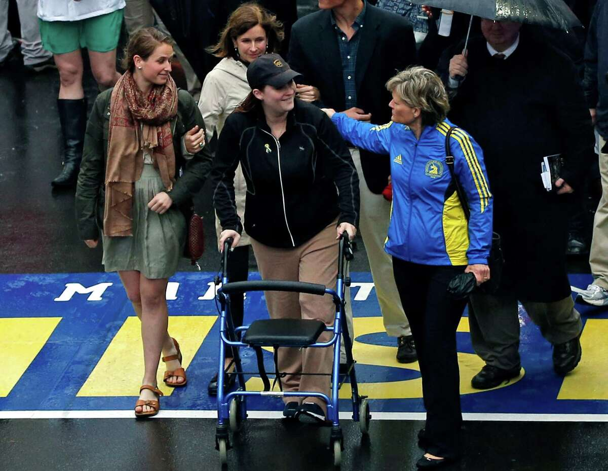 2013 Boston Marathon bombing survivor Erika Brannock, a pre-school teacher from the Baltimore area, and her mother, Carol Downing, at right, walk across the Marathon finish line after a remembrance ceremony on Boylston Street in Boston, Tuesday, April 15, 2014. (AP Photo/Elise Amendola) ORG XMIT: MAEA109