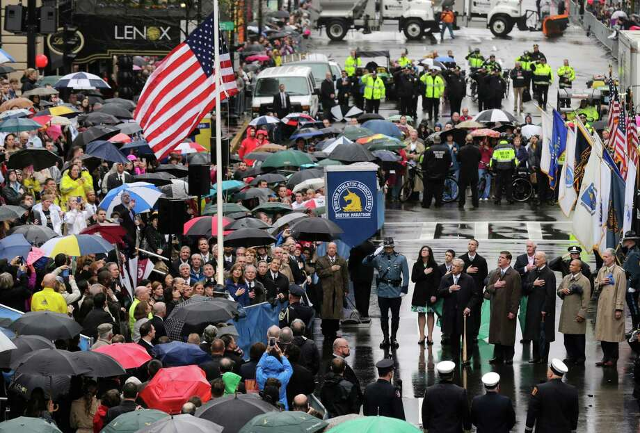 Survivors, officials, first responders and guests pause as the flag is raised at the finish line during a tribute in honor of the one year anniversary of the Boston Marathon bombings, Tuesday, April 15, 2014 in Boston. (AP Photo/Charles Krupa) ORG XMIT: MACK104 Photo: Charles Krupa / AP