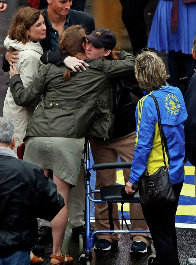 The 2013 Boston Marathon bombing survivor Erika Brannock, a pre-school teacher from the Baltimore area, second from right, is hugged as her mom, Carol Downing, watches at right after a remembrance ceremony at the Marathon finish line on Boylston Street in Boston, Tuesday, April 15, 2014. (AP Photo/Elise Amendola) ORG XMIT: MAEA103 Photo: Elise Amendola / AP