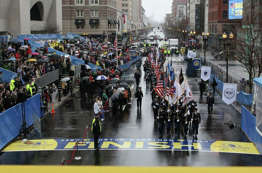 BOSTON, MA - APRIL 15:  Boston area police and fire department flag bearers cross the finish line following the flag raising ceremony commemorating the one-year anniversary of the Boston Marathon bombings on Boylston Street near the finish line on April 15, 2014 in Boston, Massachusetts.  Last year, two pressure cooker bombs killed three and injured an estimated 264 others during the Boston marathon, on April 15, 2013.  (Photo by Jared Wickerham/Getty Images) ORG XMIT: 485055841 Photo: Jared Wickerham / 2014 Getty Images