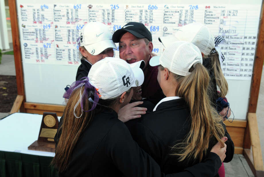 Cinco Ranch coach Rick Nordstrom, center, shares in a stirring day for his team, participating in a group hug after the squad consisting of Madison Goldblum, Sara Kelley, Kennedy Ishee, Alexis Kollmansberger, Katy Rutherford and Maddie Luitwieler wrapped up the Region III championship. Nordstrom also helped Luitwieler as she got emotional, below, after capturing the individual title. Photo: Jerry Baker, Freelance