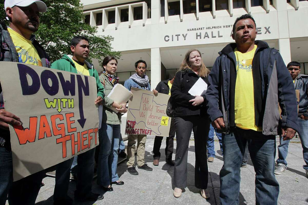 Erik Lopez, right, speaks with the media along with other construction workers gathering to file wage theft complaints with the City of Houston Office of Inspector General at the City Hall Annex on Tuesday.