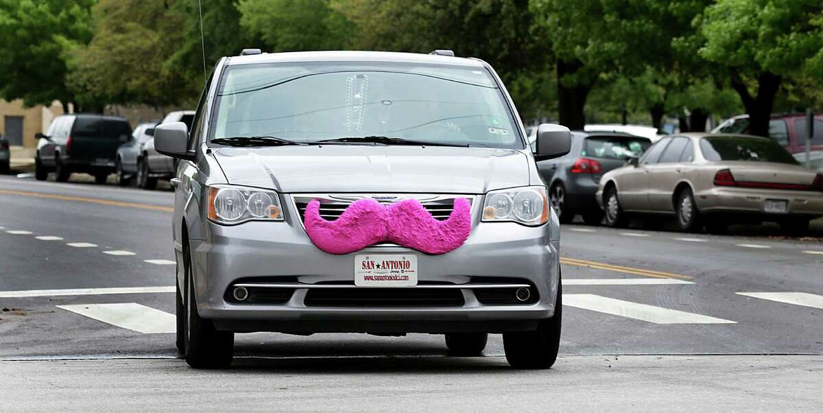 Festooned with the company's signature pink mustache, a Lyft car makes its way downtown.