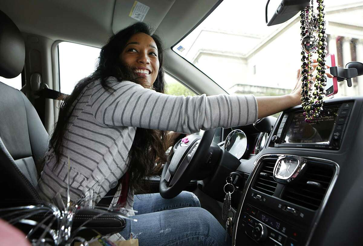 On Yong Theus a driver with LYFT, sets her GPS on her phone for directions during a fare. LYFT drivers use their own cars to drive passengers as a taxi would. Theus has decorated her car with a disco theme which was her daughter's idea. Thursday, March 27, 2014.