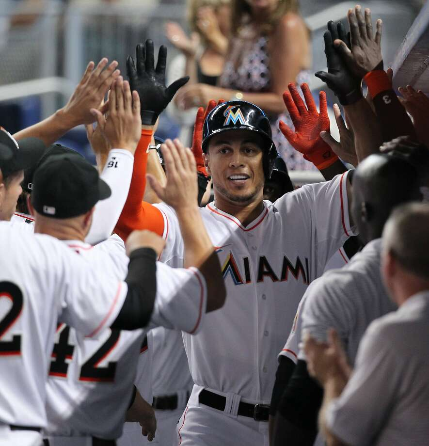 Miami Marlins right fielder Giancarlo Stanton is congratulated by his teammates after hitting a three-run homer against the Washington Nationals in the first inning on Tuesday, April 15, 2014, at Marlins Park in Miami. (David Santiago/El Nuevo Herald/MCT) Photo: David Santiago, McClatchy-Tribune News Service