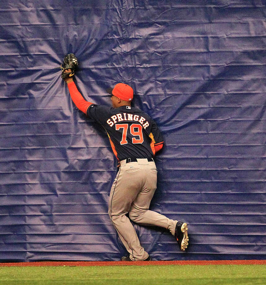Houston Astros George Springer (79)  crashes into the wall catching a fly ball hit by Rangers Jim Adduci during the eighth inning spring training game MLB baseball game at the Alamodome, Friday, March 28, 2014, in San Antonio.  ( Karen Warren / Houston Chronicle  ) Photo: Karen Warren, Houston Chronicle / © 2014 Houston Chronicle