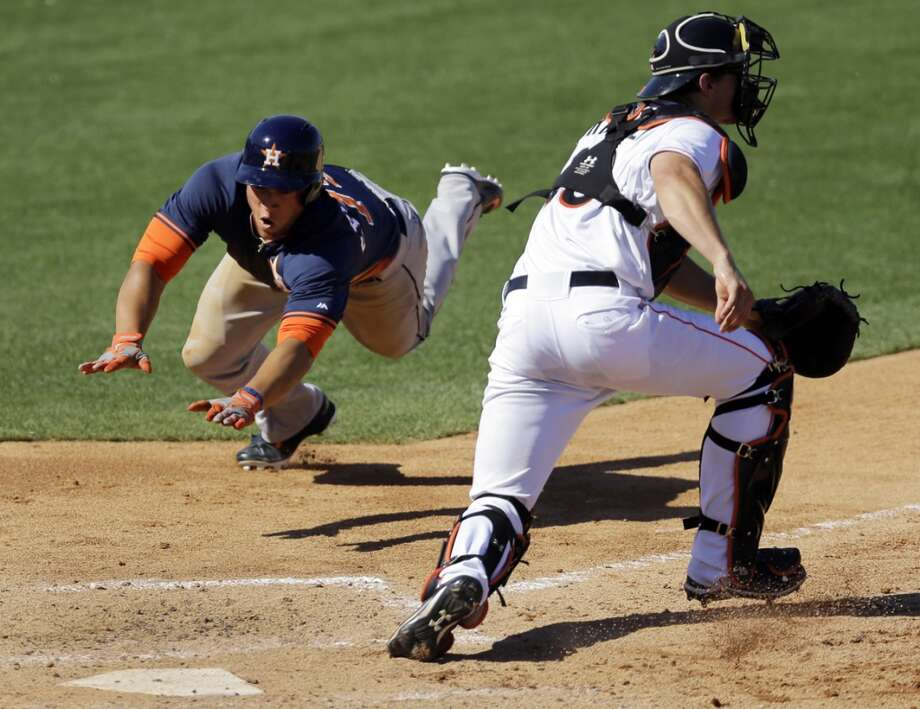 Houston Astros' George Springer, left, scores on a double by J.D. Martinez as Miami Marlins catcher Rob Brantly, right, waits for the throw during the seventh inning of an exhibition spring training baseball game Monday, March 3, 2014, in Jupiter, Fla. (AP Photo/Jeff Roberson) Photo: Jeff Roberson, Associated Press