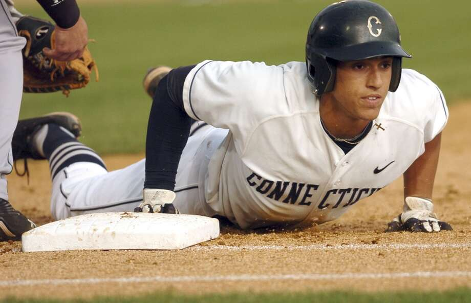 In this May 7, 2011 photo, Connecticut's George Springer dives back to first against South Florida during an NCAA college baseball game at Dodd Stadium in Norwich, Conn. The Huskies have won 26 of their last 30 games, are 18-3 in the Big East and need just two more wins in their finals six conference games to clinch their first Big East regular season title. (AP Photo/Norwich Bulletin, Tali Greener)  ** MANDATORY CREDIT ** Photo: Tali Greener, Associated Press