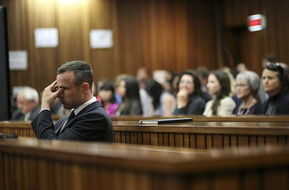 Oscar Pistorius rubs his eye in court in Pretoria, South Africa, Tuesday, April 15, 2014, after earlier questioning by state prosecutor Gerrie Nel.  Pistorius is charged with the murder of his girlfriend Reeva Steenkamp. (AP Photo/Siphiwe Sibeko, Pool) Photo: Siphiwe Sibeko, Associated Press