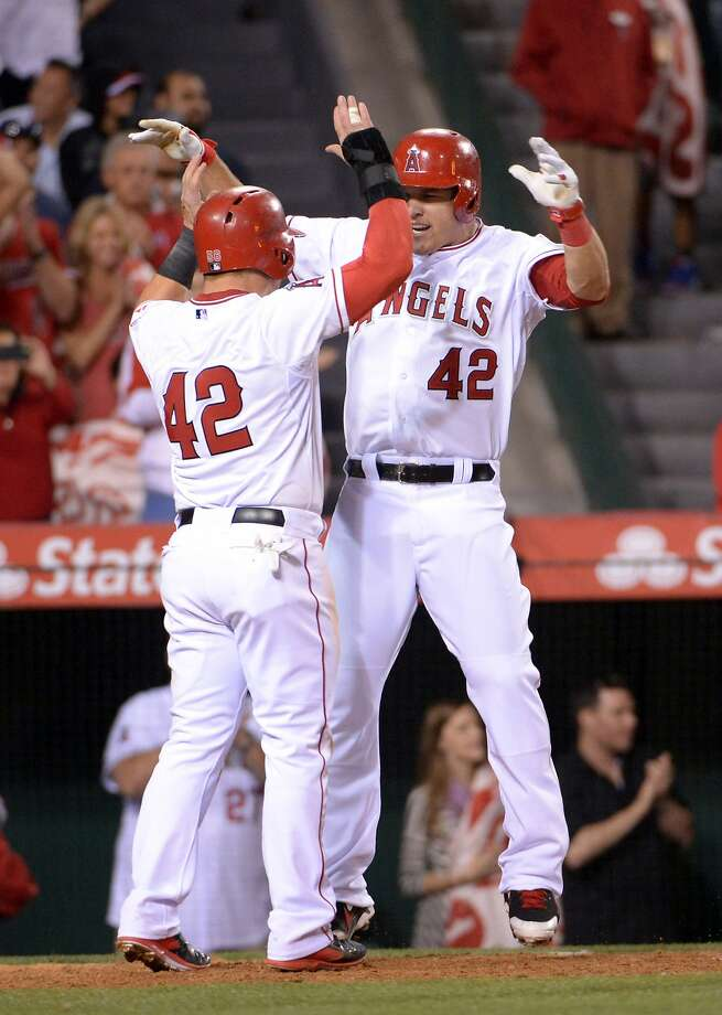 Apr 15, 2014; Anaheim, CA, USA; Los Angeles Angels center fielder Mike Trout (right) celebrates with right fielder Kole Calhoun after hitting a two-run home run in the ninth inning against the Oakland Athletics at Angel Stadium of Anaheim. Mandatory Credit: Kirby Lee-USA TODAY Sports Photo: Kirby Lee, Reuters
