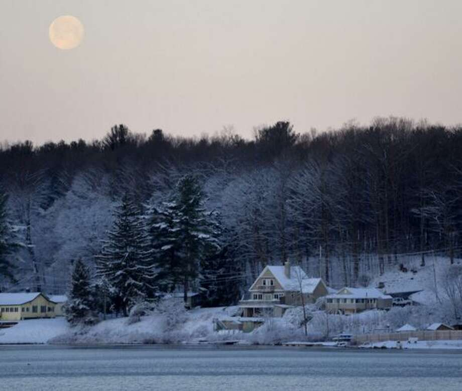 The moon sets over a frigid Saratoga Lake on Wednesday, April 16, 2014. The area was covered with an inch of snow overnight. (Skip Dickstein / Times Union)