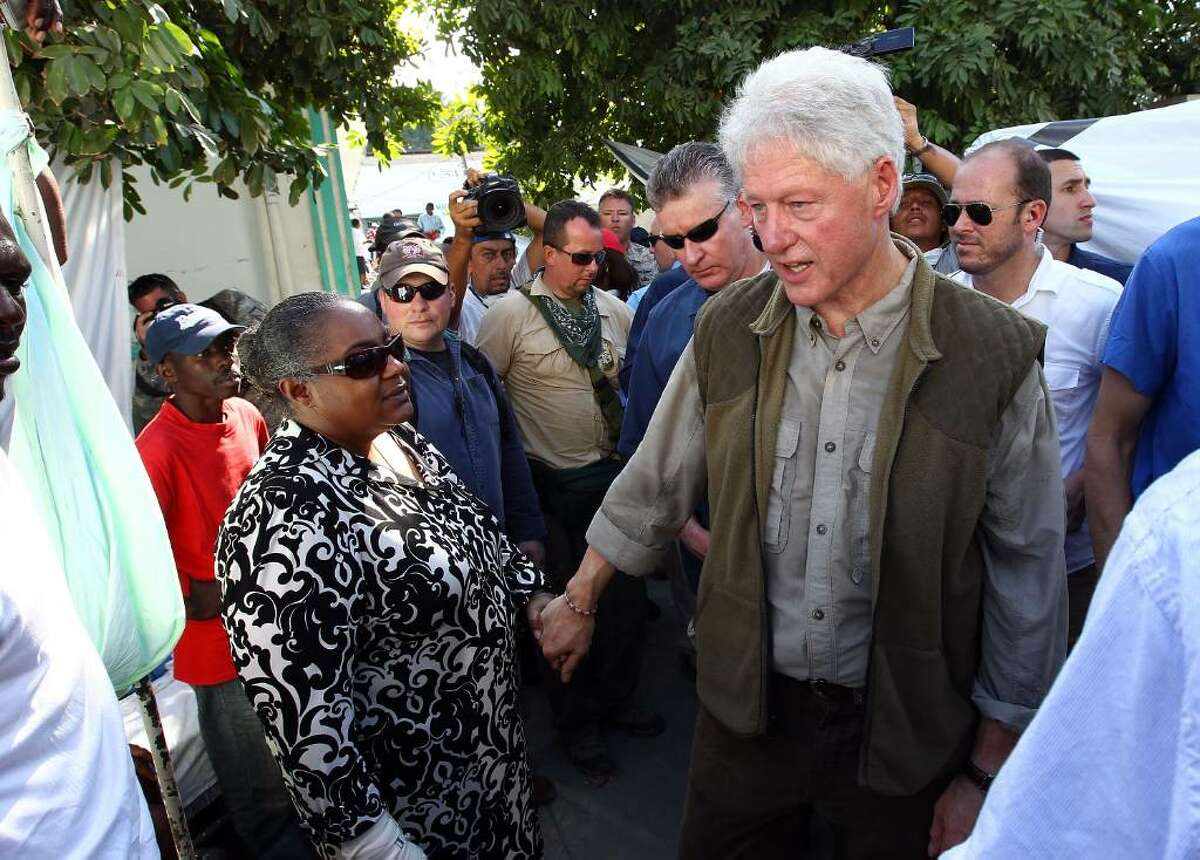 PORT-AU-PRINCE, HAITI - JANUARY 18: Former U.S. President Bill Clinton greets an injured woman at the Central Hospital January 18, 2010 in Port-au-Prince, Haiti. The Haitian capital continues to struggle with the effects of a devastating earthquake that took place six days ago. (Photo by Win McNamee/Getty Images) *** Local Caption *** Bill Clinton