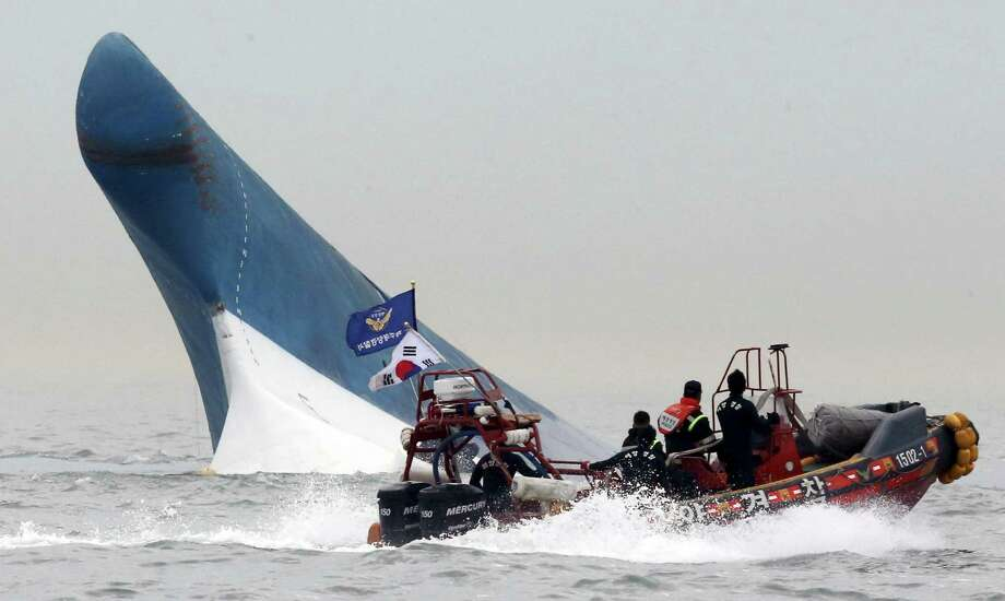 South Korean coast guard officers try to rescue passengers from a ferry sinking in the water off the southern coast near Jindo, south of Seoul, South Korea, Wednesday, April 16, 2014. The ferry carrying 459 people, mostly high school students on an overnight trip to a tourist island, sank off South Korea's southern coast on Wednesday, leaving nearly 300 people missing despite a frantic, hours-long rescue by dozens of ships and helicopters. At least four people were confirmed dead and 55 injured.  KOREA OUT Photo: Yonhap, AP / YONHAP