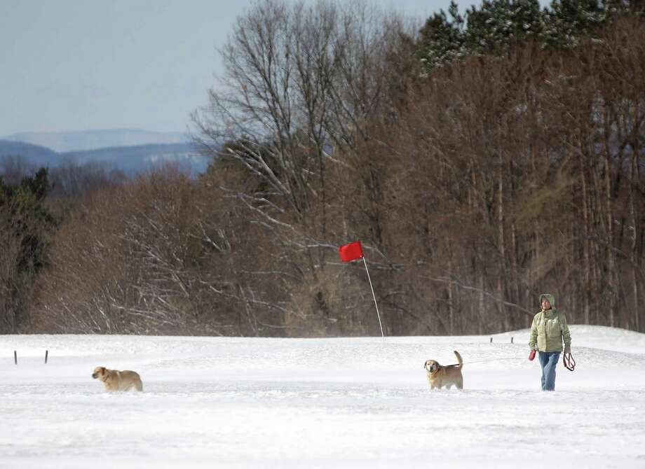 Maura McPeak of Guilderland, N.Y., walks her dogs Blaze and Misty on the driving range at Capital Hills golf course on Wednesday, April 16, 2014, in Albany, N.Y. The course has not opened for the season. A cold front swept across the region Tuesday dumping several inches of snow in parts of upstate New York and an icy dusting in New York City overnight. (AP Photo/Mike Groll) ORG XMIT: NYMG103 Photo: Mike Groll, AP / AP