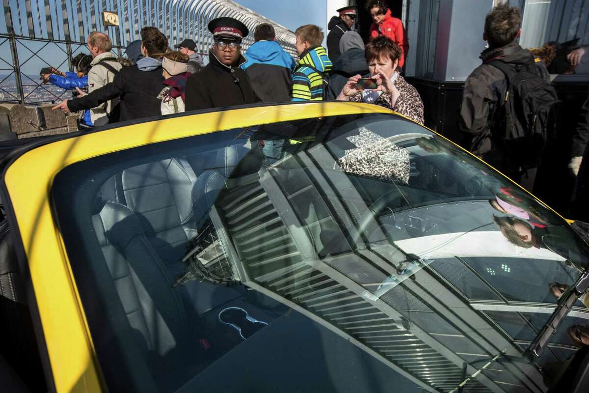 The spire of the Empire State Building is reflected in the windshield of the all-new 2015 Mustang convertible as it's revealed by the Ford Motor Company on the 86th floor observation deck during the New York International Auto Show, Wednesday, April 16, 2014, in New York. (AP Photo/John Minchillo) ORG XMIT: NYJM115
