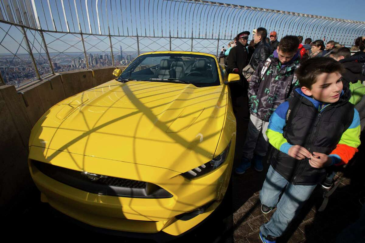 People walk past the all-new 2015 Mustang convertible as it's revealed by the Ford Motor Company on the 86th floor observation deck during the New York International Auto Show, Wednesday, April 16, 2014, in New York. (AP Photo/John Minchillo) ORG XMIT: NYJM116