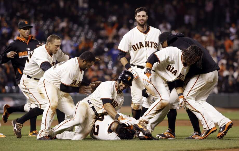 San Francisco Giants' Hector Sanchez, bottom center, is mobbed by teammates after driving in the game-winning run during the 12th inning of a baseball game against the Los Angeles Dodgers on Wednesday, April 16, 2014, in San Francisco. San Francisco won 3-2. Photo: Marcio Jose Sanchez, Associated Press