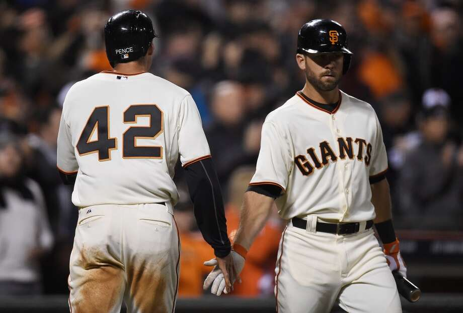 Hunter Pence (left) of the San Francisco Giants is congratulated by Brandon Hicks (right) after Pence scored on a sacrifice fly by Brandon Crawford (not pictured) against the Los Angeles Dodgers in the bottom of the six inning at AT&T Park on April 15, 2014 in San Francisco, California. All uniformed team members are wearing jersey number 42 in honor of Jackie Robinson Day. Photo: Thearon W. Henderson, Getty Images