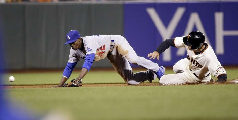 San Francisco Giants' Hunter Pence, right, is safe at second as Los Angeles Dodgers second baseman Dee Gordon, left, misses the throw to the base after a ground ball from Michael Morse during the sixth inning of a baseball game on Tuesday, April 15, 2014, in San Francisco. Photo: Marcio Jose Sanchez, Associated Press