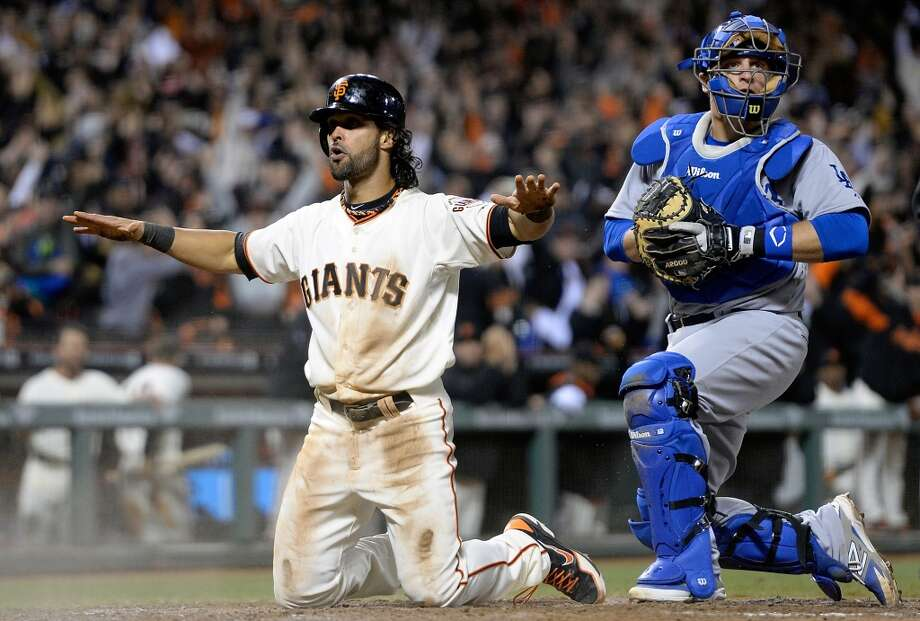 Angel Pagan of the San Francisco Giants reacts after he scored the tying run in the bottom of the ninth inning as catcher Tim Fedorwicz of the Los Angeles Dodgers looks on at AT&T Park on April 15, 2014 in San Francisco, California. Every team member is wearing the jersey #42 in honor of Jackie Robinson Day. Photo: Thearon W. Henderson, Getty Images