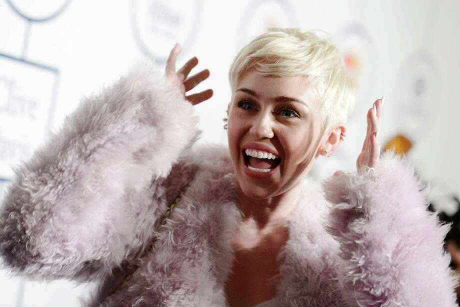 "FILE - In this Jan. 25, 2014 file photo, Miley Cyrus arrives at the 56th annual GRAMMY awards - salute to industry icons with Clive Davis, in Beverly Hills, Calif. Cyrus is in the hospital and unable to perform her ""Bangerz"" concert at Kansas City's Sprint Center as planned. A Cyrus spokeswoman says the 21-year-old entertainer canceled her performance Tuesday, April 15, 2014, after she was hospitalized for a severe allergic reaction to antibiotics. (Photo by Dan Steinberg/Invision/AP, file) Photo: Dan Steinberg, Dan Steinberg/Invision/AP / Invision"
