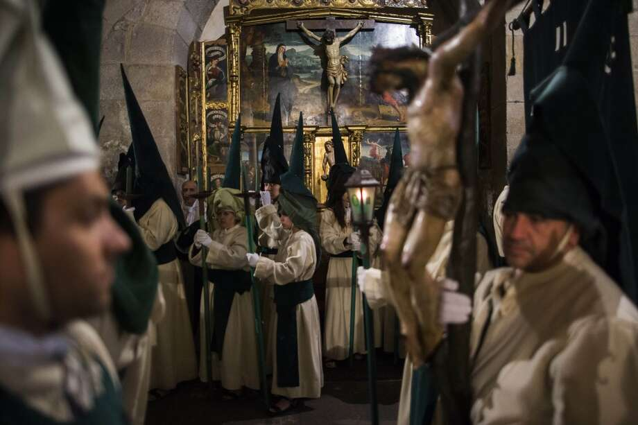 Penitents from 'Las Siete Palabras', 'Seven words' brotherhood get ready as they take part in a procession in Zamora, Spain, on the early hours of Wednesday, April 16, 2014. Hundreds of processions take place throughout Spain during the Easter Holy Week. Photo: Andres Kudacki, Associated Press
