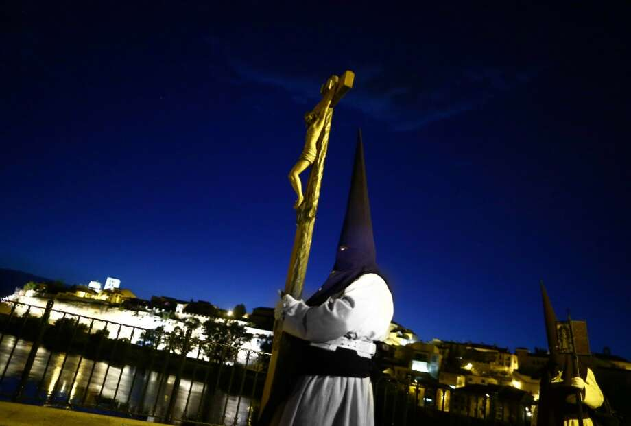 """Penitents from """"Jesus del Via Crucis"""" brotherhood cross a bridge as they take part in a procession in Zamora, Spain, Tuesday, April 15, 2014. Hundreds of processions take place throughout the country during the Easter Holy Week. Photo: Andres Kudacki, Associated Press"""