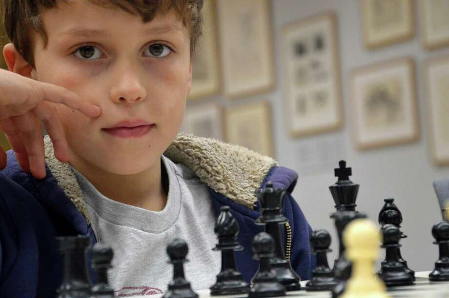 Angus Lawrie, 8, of Westport -- at a recent session of the Westport LIbrary's Chess Club for young players -- finds chess a challenging but fun game. Photo: Jarret Liotta / Fairfield Citizen
