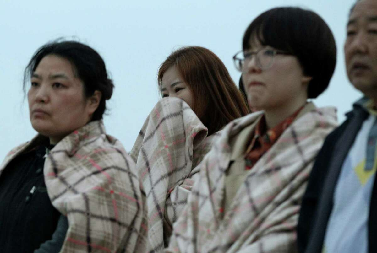 Relatives of passengers of a sunken ship wrapped in blankets look toward the sea at Jindo port, South Korea, Wednesday, April 16, 2014. The ferry carrying 459 people, mostly high school students on an overnight trip to a tourist island, sank off South Korea's southern coast on Wednesday, leaving nearly 300 people missing despite a frantic, hours-long rescue by dozens of ships and helicopters. (AP Photo/Ahn Young-joon) ORG XMIT: SEL113