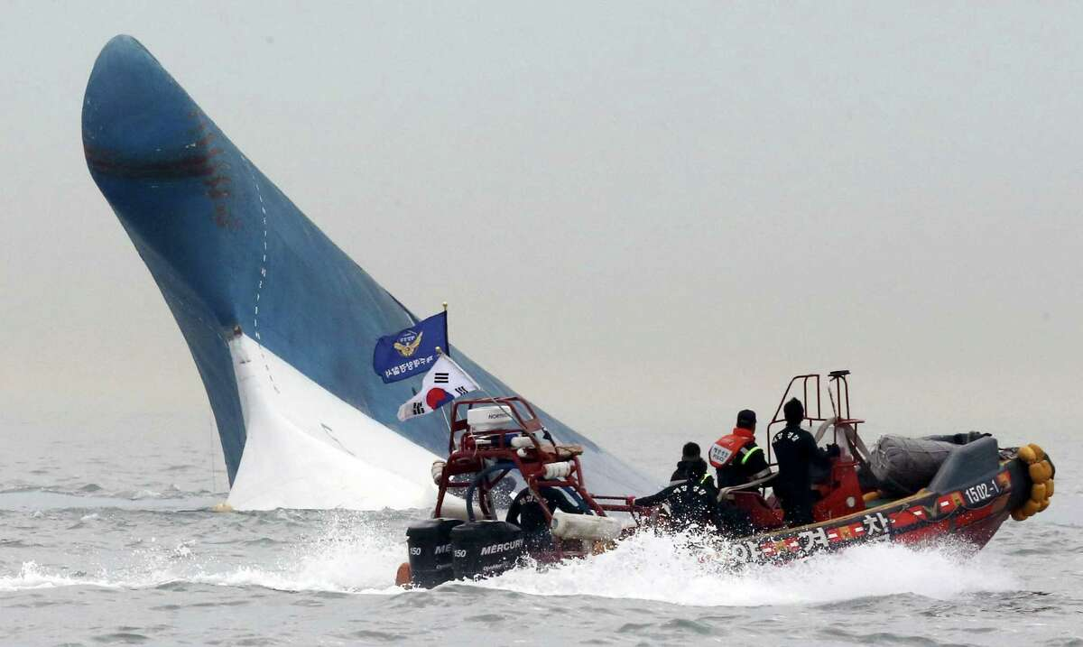 South Korean coast guard officers try to rescue passengers from a ferry sinking in the water off the southern coast near Jindo, south of Seoul, South Korea, Wednesday, April 16, 2014. The ferry carrying 459 people, mostly high school students on an overnight trip to a tourist island, sank off South Korea's southern coast on Wednesday, leaving nearly 300 people missing despite a frantic, hours-long rescue by dozens of ships and helicopters. At least four people were confirmed dead and 55 injured. (AP Photo/Yonhap) KOREA OUT ORG XMIT: SEL826