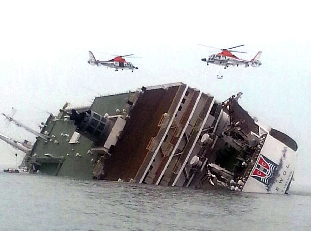 Rescue helicopters fly over a sinking South Korean passenger ferry that was carrying more than 450 passengers, mostly high school students, Wednesday, April 16, 2014, off South Korea's southern coast. Hundreds of people are missing despite a frantic, hours-long rescue by dozens of ships and helicopters. At least four people were confirmed dead and 55 injured. (AP Photo/Yonhap) KOREA OUT ORG XMIT: NY201