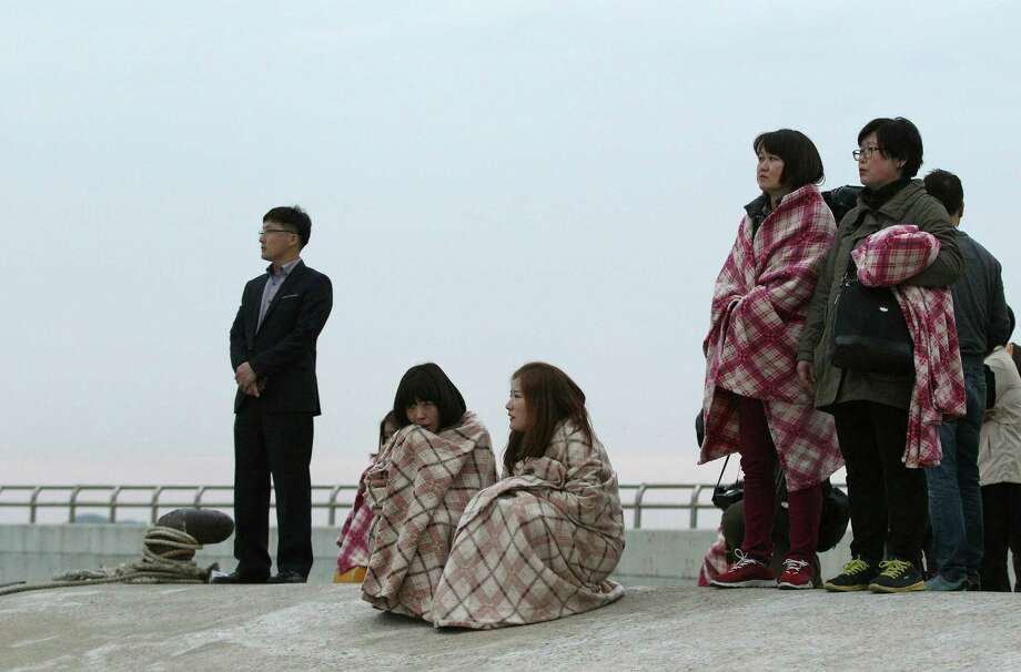 Relatives wait for their missing loved ones at a port in Jindo, South Korea, Wednesday, April 16, 2014. A ferry carrying 459 people, mostly high school students on an overnight trip to a tourist island, sank off South Korea's southern coast on Wednesday, leaving nearly 300 people missing despite a frantic, hours-long rescue by dozens of ships and helicopters. (AP Photo/Ahn Young-joon) ORG XMIT: SEL106 Photo: Ahn Young-joon, AP / AP