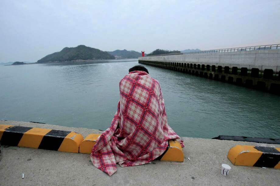 A relative waits for their missing loved one at a port in Jindo, South Korea, Wednesday, April 16, 2014. A ferry carrying 459 people, mostly high school students on an overnight trip to a tourist island, sank off South Korea's southern coast on Wednesday, leaving nearly 300 people missing despite a frantic, hours-long rescue by dozens of ships and helicopters. (AP Photo/Ahn Young-joon) ORG XMIT: SEL108 Photo: Ahn Young-joon, AP / AP