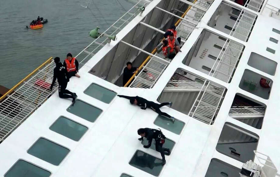 **EDS: HIGHEST RESOLUTION POSSIBLE** Rescue workers, in black, help passengers as the South Korean ferry Sewol sinks off South Korea's coast, April 16, 2014. Fears increased Wednesday as rescued passengers said they believed many people had been trapped as the ship went down, and more than 290 people were still unaccounted for. (Korean Coast Guard via The New York Times) -- FOR EDITORIAL USE ONLY. -- ORG XMIT: XNYT13 Photo: KOREAN COAST GUARD, New York Times / KOREAN COAST GUARD