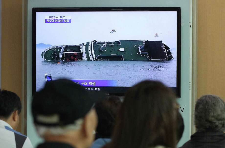 People watch a TV news program showing a sinking passenger ship, at Seoul Railway Station in Seoul, South Korea, Wednesday, April 16, 2014. The South Korean passenger ship carrying more than 470 people, including many high school students, is sinking off the country's southern coast Wednesday after sending a distress call, officials said. There are no immediate reports of causalities.(AP Photo/Ahn Young-joon) ORG XMIT: SEL101 Photo: Ahn Young-joon, AP / AP