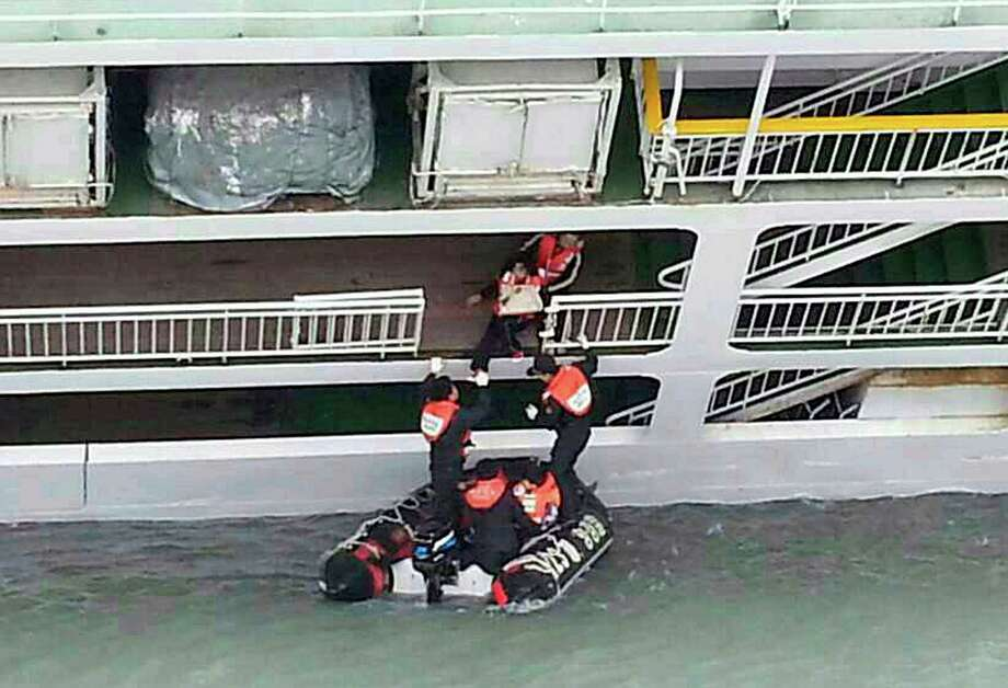 In this photo released by the South Korean Coast Guard via Yonhap News Agency, South Korean coast guard officers rescue passengers from a sinking ferry off the southern coast near Jindo, south of Seoul, South Korea, Wednesday, April 16, 2014. A ferry carrying 459 people, mostly high school students on an overnight trip to a tourist island, sank off South Korea's southern coast on Wednesday, leaving nearly 300 people missing despite a frantic, hours-long rescue by dozens of ships and helicopters.  (AP Photo/South Korea Coast Guard via Yonhap) KOREA OUT ORG XMIT: SEL827 Photo: AP / South Korea Coast Guard via YONHAP