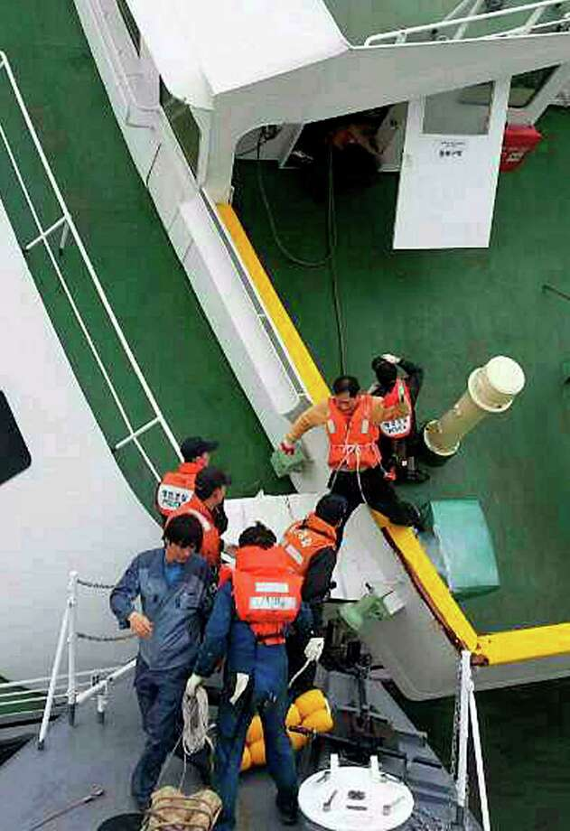 In this photo released by South Korea Coast Guard via Yonhap News Agency, South Korean coast guard rescue passengers from a ferry in the water off the southern coast near Jindo, South Korea, Wednesday, April 16, 2014. The ferry carrying 459 people, mostly high school students on an overnight trip to a tourist island, sank off South Korea's southern coast on Wednesday, leaving nearly 300 people missing despite a frantic, hours-long rescue by dozens of ships and helicopters. (AP Photo/South Korea Coast Guard via Yonhap) KOREA OUT ORG XMIT: SEL828 Photo: AP / South Korea Coast Guard Via Yonhap