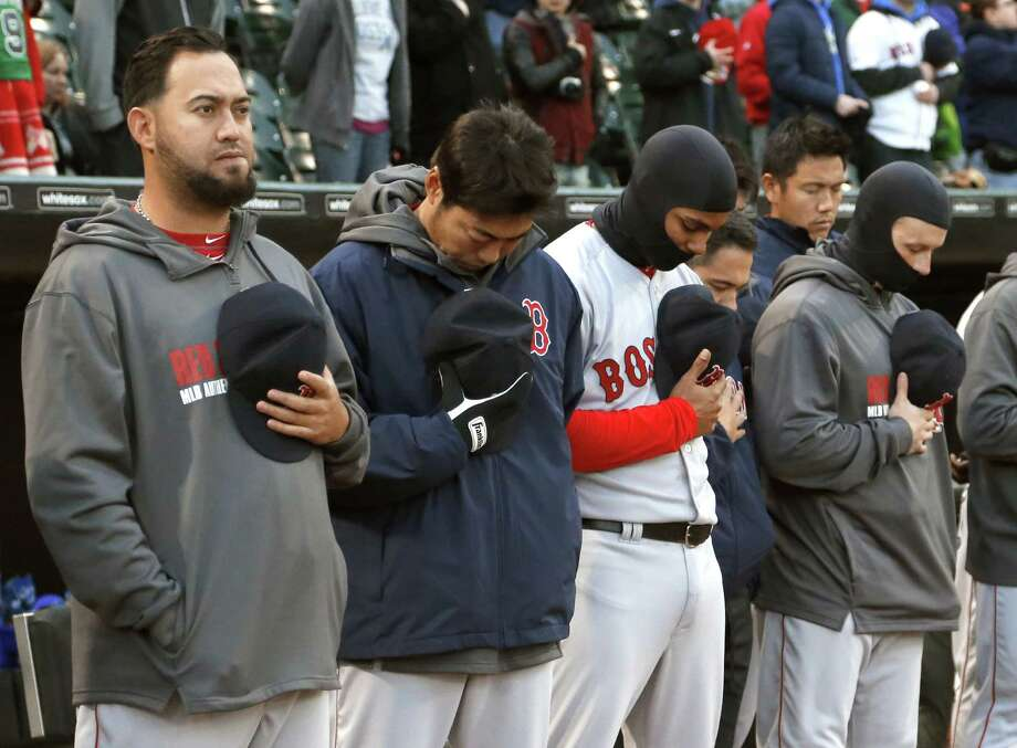 Members of the Boston Red Sox stand for a moment of silence for the victims of the Boston Marathon bombings, befor ethe Red Sox's baseball game against the Chicago White Sox on Tuesday, April 15, 2014, in Chicago. (AP Photo/Charles Rex Arbogast) ORG XMIT: CXS103 Photo: Charles Rex Arbogast, AP / AP