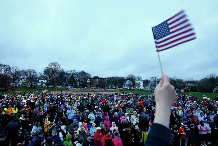 BOSTON, MA - APRIL 15: Kids wave their American flags at the start of a candlelight vigil for the one-year anniversary of the Boston Marathon bombings at Garvey Park on April 15, 2014 in Boston, Massachusetts. Last year, two pressure cooker bombs killed three and injured an estimated 264 others during the Boston marathon, on April 15, 2013.  (Photo by Jared Wickerham/Getty Images) ORG XMIT: 485055841 Photo: Jared Wickerham, Getty / 2014 Getty Images