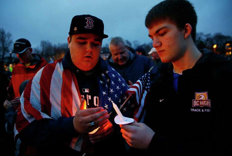 BOSTON, MA - APRIL 15: Two Dorchester residents light their candles during the candlelight vigil for the one-year anniversary of the Boston Marathon bombings at Garvey Park on April 15, 2014 in Boston, Massachusetts. Last year, two pressure cooker bombs killed three and injured an estimated 264 others during the Boston marathon, on April 15, 2013.  (Photo by Jared Wickerham/Getty Images) ORG XMIT: 485055841 Photo: Jared Wickerham, Getty / 2014 Getty Images