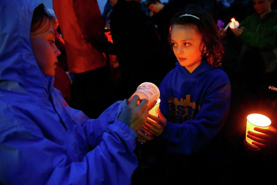 BOSTON, MA - APRIL 15: Two young girls light each others candles during a candlelight vigil for the one-year anniversary of the Boston Marathon bombings at Garvey Park on April 15, 2014 in Boston, Massachusetts. Last year, two pressure cooker bombs killed three and injured an estimated 264 others during the Boston marathon, on April 15, 2013.  (Photo by Jared Wickerham/Getty Images) ORG XMIT: 485055841 Photo: Jared Wickerham, Getty / 2014 Getty Images
