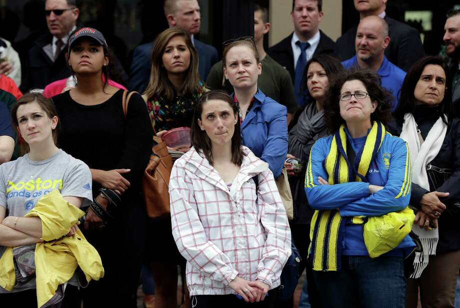 Heather McDade of Boston, center, reacts while watching a tribute ceremony with others on an over-sized outdoor monitor, Tuesday, April 15, 2014, on Boylston Street in Boston. The ceremony was held for those killed and injured in the bombings at the finish line of the Boston Marathon a year ago. (AP Photo/Steven Senne) ORG XMIT: MASR102 Photo: Steven Senne, AP / AP