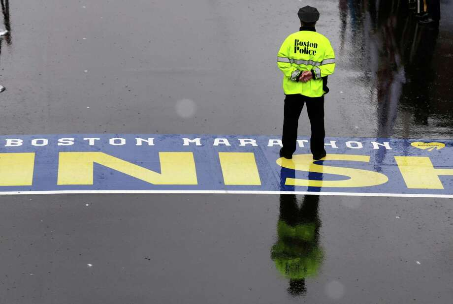 A Boston police officer pauses on the finish line during a tribute in honor of the one year anniversary of the Boston Marathon bombings, Tuesday, April 15, 2014 in Boston. (AP Photo/Charles Krupa) ORG XMIT: MACK112 Photo: Charles Krupa, AP / AP