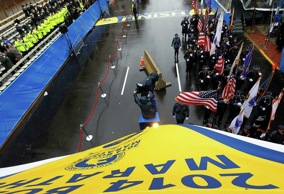 BOSTON, MA - APRIL 15: Boston area police and fire department flag bearers cross the finish line following the flag raising ceremony commemorating the one-year anniversary of the Boston Marathon bombings on Boylston Street near the finish line on April 15, 2014 in Boston, Massachusetts.  Last year, two pressure cooker bombs killed three and injured an estimated 264 others during the Boston marathon, on April 15, 2013.  (Photo by Jared Wickerham/Getty Images) ORG XMIT: 485055841 Photo: Jared Wickerham, Getty / 2014 Getty Images
