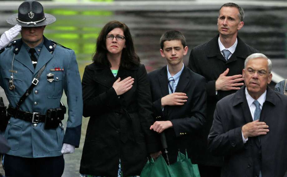 The family of 2013 Boston Marathon bombing victim Martin Richard, from left, mother Denise, brother Henry, and father Bill Richard, place their hands over their hearts as they stand with former Boston Mayor Tom Menino, right, during a tribute in honor of the one year anniversary of the Boston Marathon bombings, Tuesday, April 15, 2014 in Boston. At left is a Mass. State Trooper. (AP Photo/Charles Krupa) ORG XMIT: MACK115 Photo: Charles Krupa, AP / AP