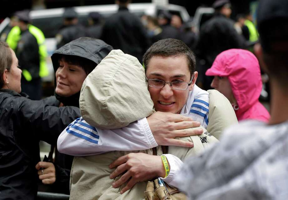 Alex Fusco, of North Reading, Mass., right, hugs his mother Ernestine Fusco, center, at the conclusion of tribute ceremonies near the finish line of the Boston Marathon, Tuesday, April 15, 2014, in Boston. Alex, who was working as an athletic trainer near the finish line April 15, 2013, was among first responders to the scene of the bombing. (AP Photo/Steven Senne)  ORG XMIT: MASR108 Photo: Steven Senne, AP / AP