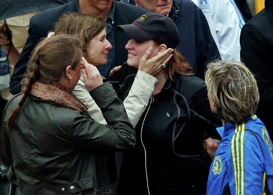 2013 Boston Marathon bombing survivor Erika Brannock, in hat, a pre-school teacher from the Baltimore area, is embraced as she walks across the Marathon finish line after a remembrance ceremony on Boylston Street in Boston, Tuesday, April 15, 2014. (AP Photo/Elise Amendola) ORG XMIT: MAEA110 Photo: Elise Amendola, AP / AP